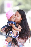 Asian woman holding and kissing baby Stock Image