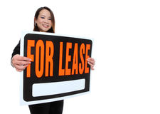 Asian Woman Holding Lease Sign. A cute young asian woman holding a lease sign isolated over white Royalty Free Stock Photo