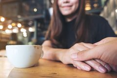 Asian woman holding a man`s hand with feeling love and warmness. An Asian woman holding a man`s hand with feeling love and warmness Stock Photography