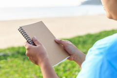 Asian woman holding notebook on the beach Stock Image