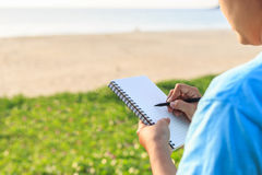 Asian woman holding notebook with pencil and writing Stock Images