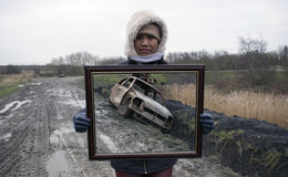 Asian Woman Holding Picture Frame With Stolen & Burnt Out Car Trick Photography. Royalty Free Stock Images