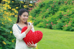 Asian woman holding a red heart Stock Images