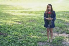 An Asian woman holding red roses bouquet on grass field Royalty Free Stock Photo