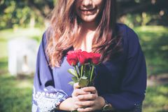 An Asian woman holding red roses bouquet with green nature. Background Stock Image