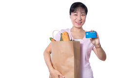 Asian woman holding a shopping bag full of groceries and credit. Card in hands in isolated White Background Royalty Free Stock Images