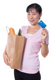 Asian woman holding a shopping bag full of groceries and credit. Card in hands in isolated White Background Royalty Free Stock Image