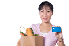Asian woman holding a shopping bag full of groceries and credit. Card in hands in isolated White Background Royalty Free Stock Photos