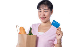 Asian woman holding a shopping bag full of groceries and credit. Card in hands in isolated White Background Stock Photos