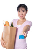 Asian woman holding a shopping bag full of groceries and credit. Card in hands in isolated White Background Stock Images
