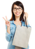 Asian woman holding shopping bag with victory sign Stock Photo