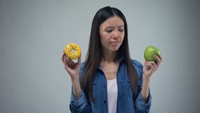 Asian woman holding sweet greasy donut and juicy green apple in hands, decision. Stock footage stock footage