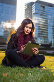 Asian woman holding tablet in hand, sitting instanding outdoors behind skyscrapers Stock Photos