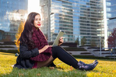 Asian woman holding tablet in hand, sitting instanding outdoors behind skyscrapers Royalty Free Stock Photo