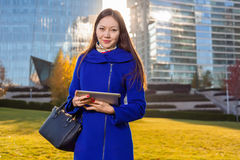 Asian woman holding tablet in hand, standing instanding outdoors behind skyscrapers Stock Images