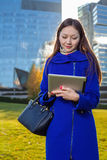 Asian woman holding tablet in hand, standing instanding outdoors behind skyscrapers Royalty Free Stock Photography