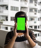 Asian woman holding tablet in her hands with white building in the background. Asian woman holding tablet in her hands in front of her face with blank green Stock Images