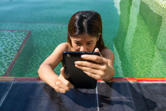 Asian woman holding tablet in the swimming pool area Royalty Free Stock Image