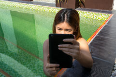 Asian woman holding tablet in the swimming pool Stock Photography