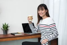Asian woman holding take away coffee cup and using laptop at cafe restaurant near window see through garden,Digital age lifestyle. Working outside office stock photography