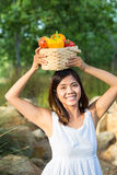 Asian woman holding on top of her head a basket of bell peppers and mango Stock Photos