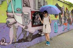 Asian woman holding umbrella near street art Royalty Free Stock Photos