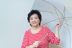 Asian woman holding umbrella in studio shot, specialty tones Stock Image