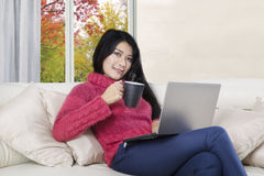 Asian woman holds hot coffee and laptop Stock Image