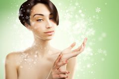 Beautiful asian woman holds a product on snowy background royalty free stock photography