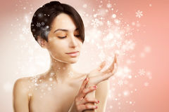 Asian woman holds a product on snowy background Royalty Free Stock Photo