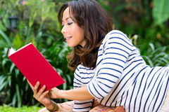Asian woman at home in garden reading book Royalty Free Stock Photos
