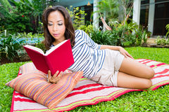 Asian woman at home in garden reading book Stock Image