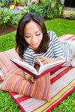 Asian woman at home in garden reading book Stock Images