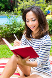 Asian woman at home in garden reading book Stock Photo