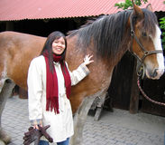 Asian woman with horse. Close up of smiling Asian woman stroking horse Royalty Free Stock Photo