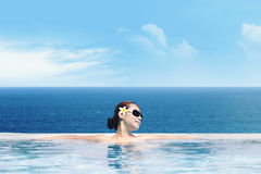 Asian woman in infinity pool Royalty Free Stock Photos