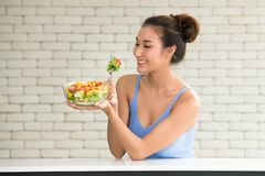 Asian woman in joyful postures with hand holding salad stock photography