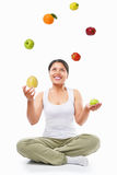 Asian woman juggling fruits Royalty Free Stock Photo