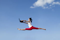 Asian woman jumping with laptop Stock Images
