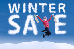 Asian woman jumping make the word winter sale. On the sky Royalty Free Stock Image