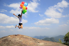 Asian woman jumping on mountain peak rock with colored balloons Royalty Free Stock Photos