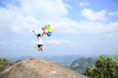 Asian woman jumping on mountain peak rock with colored balloons Stock Images