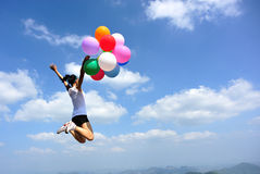 Asian woman jumping on mountain peak rock with colored balloons Royalty Free Stock Photography