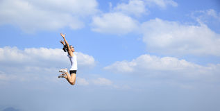 Asian woman jumping on mountain peak rock Royalty Free Stock Photography
