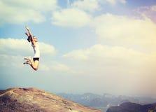 Asian woman jumping on mountain peak rock Royalty Free Stock Photography