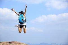 Asian woman jumping on mountain peak rock Royalty Free Stock Images