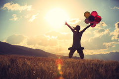 Asian woman jumping on sunset grassland with colored balloons Stock Images