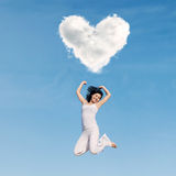Asian woman jumping under heart cloud. Asian woman jumping happily under heart cloud Royalty Free Stock Photography