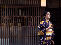 Asian woman in kimono in Higashichaya geisha district of Kanazawa. Kanazawa, Japan - September 29, 2015: Asian women in colorful kimono holding sellphone in Royalty Free Stock Images