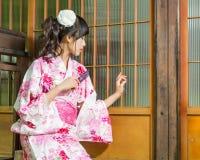 Asian woman in kimono holding fan looking faint Royalty Free Stock Photography